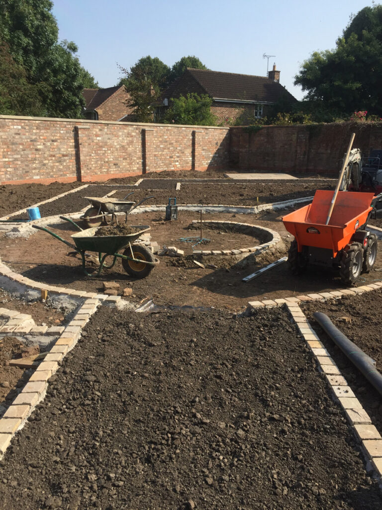 Construction of round feature with planted beds surrounding it