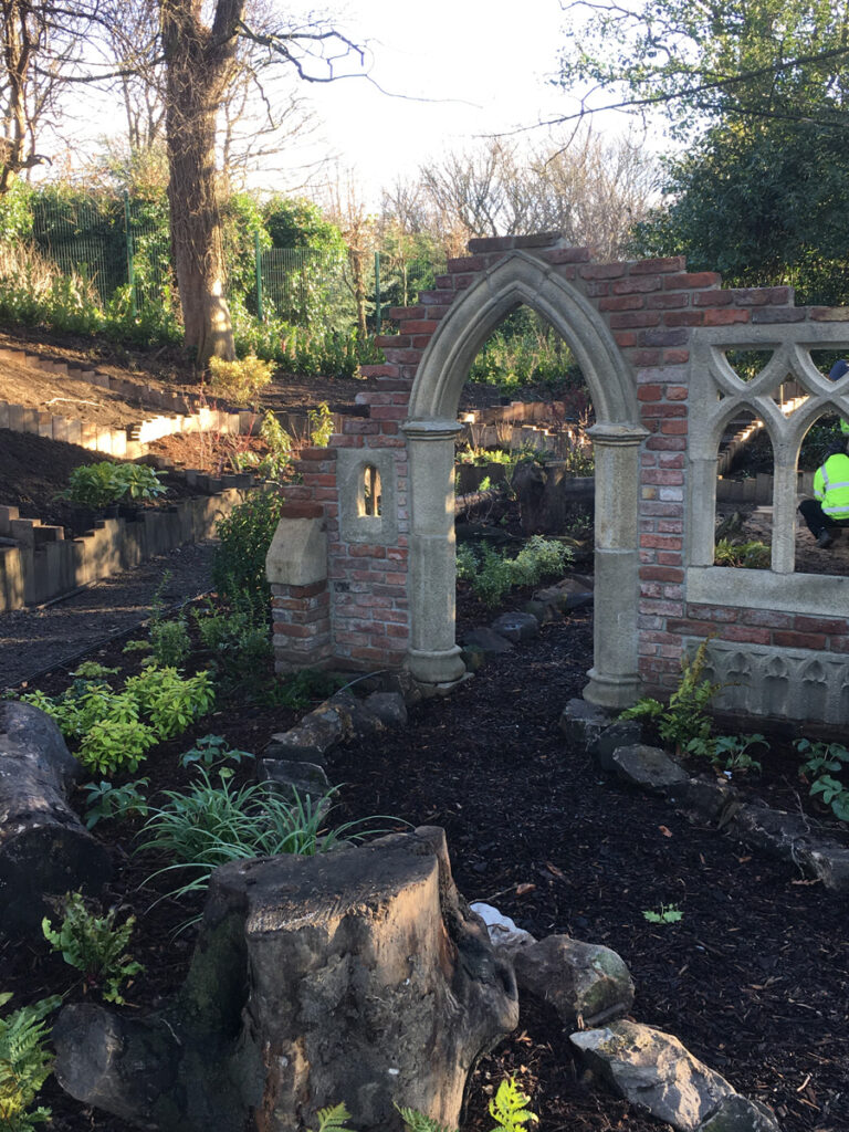 Planted garden beds surrounding a stone archway feature