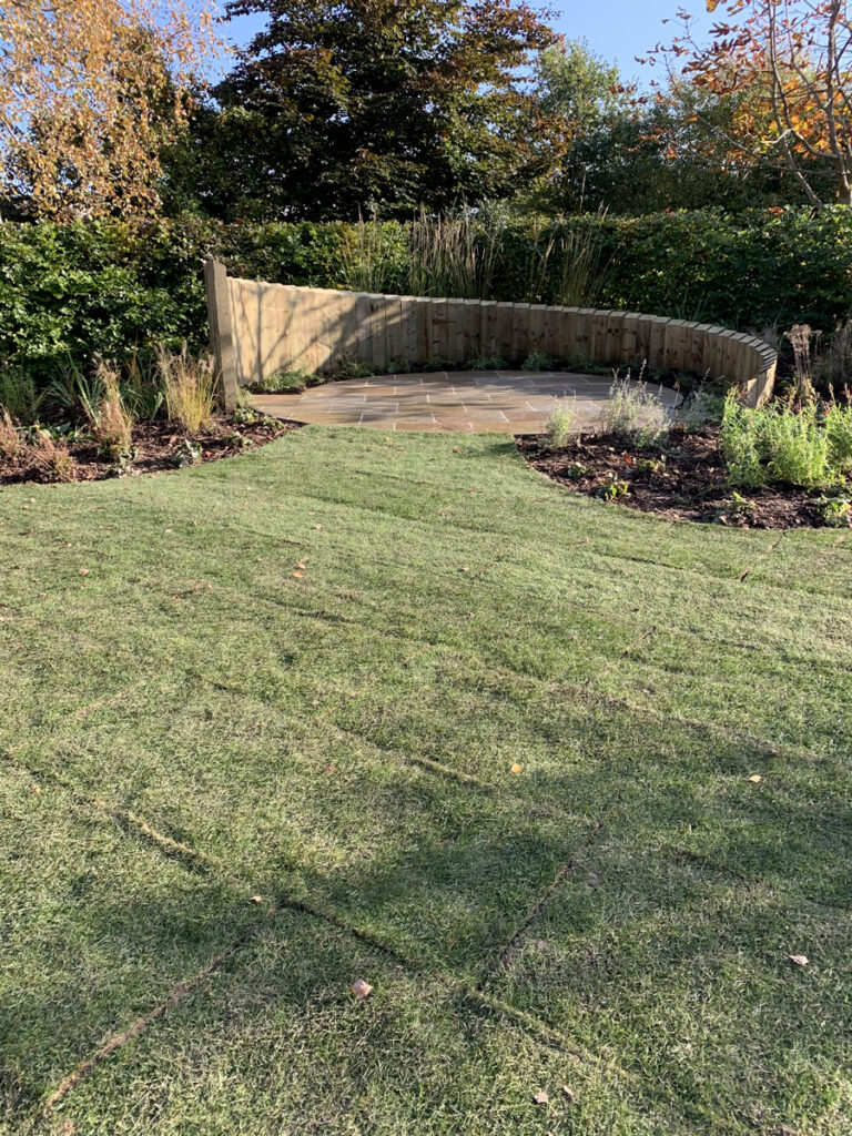Newly laid lawn leading to circular feature patio