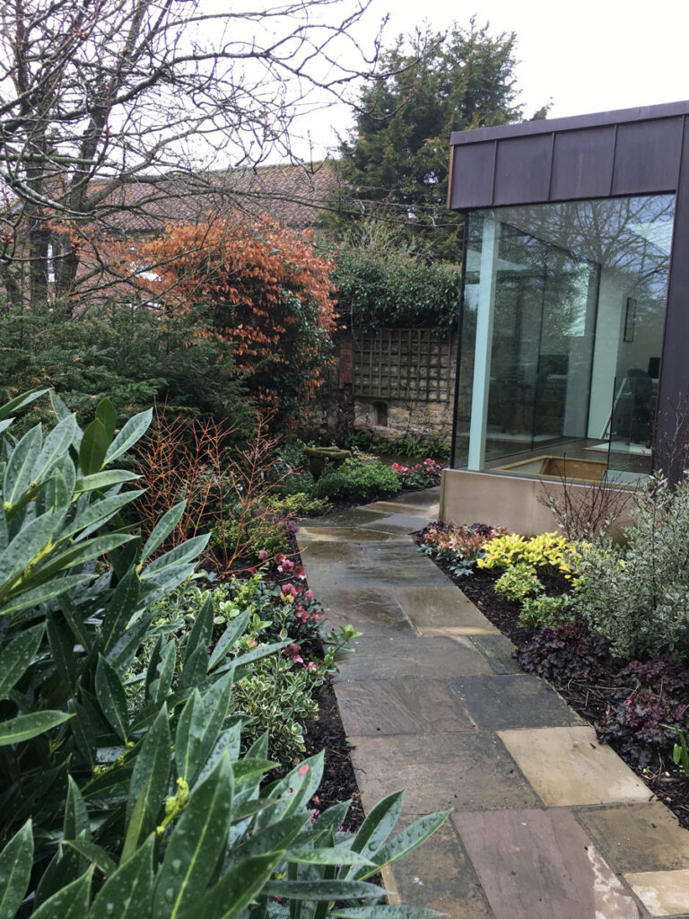 Stone paved path leading between newly planted garden beds